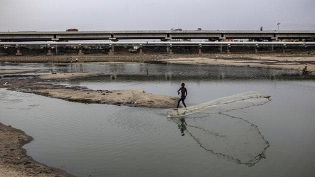 A man casts a fishing net in the depleted Porur Lake. The administration of Prime Minister Narendra Modi, who promised an ambitious healthcare expansion ahead of his re-election in May, announced a water conservation awareness program on July 1. Yet it's unclear if the measures will be enough to ensure a steady supply of clean water. (Dhiraj Singh / Bloomberg)