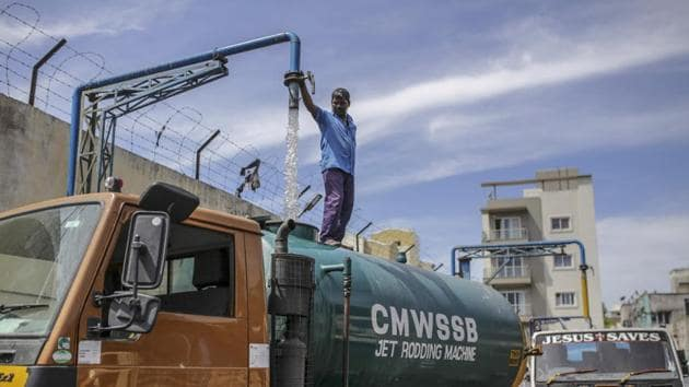A water tank operator pours water from a pipe into a water tanker at a government-run filling station in Chennai. The water shortages risk further hurting the already struggling state-run health system. India spends only around 1% of GDP on healthcare, and aims to increase it to 2.5% by 2025. (Dhiraj Singh / Bloomberg)