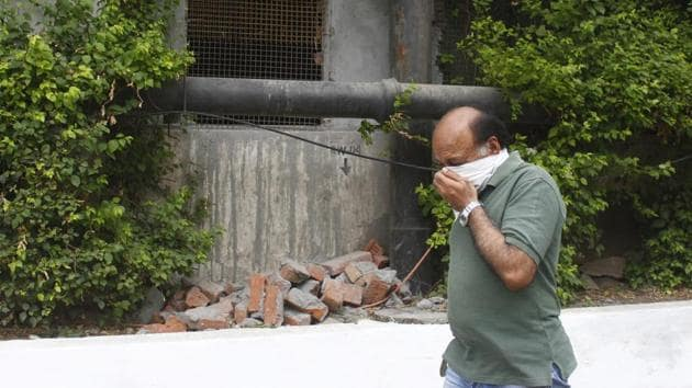 A DLF-2 resident covers his face while walking past the sewage treatment plant at DLF Cyber City.(Yogendra Kumar/HT PHOTO)