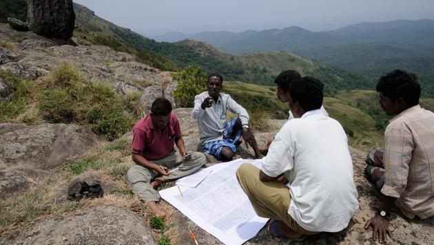 A group of Soliga adivasis in the process of producing a counter-map of the Biligiri Rangaswamy Temple Tiger Reserve, Karnataka. ATREE'S long-term ecological work in BRT shows that restrictions on the use of forests by resident adivasis violates their rights and have several adverse ecological and social outcomes.(NITIN RAI)