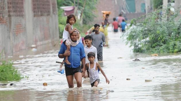 People moving to safer places after water entered their houses in the Gopal Colony locality of Patiala, Punjab, on Tuesday, July 16, 2019.(Bharat Bhushan / HT Photo)