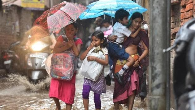 School children on a waterlogged road in Delhi's Patel Nagar on Wednesday.(Sanchit Khanna/HT Photo)