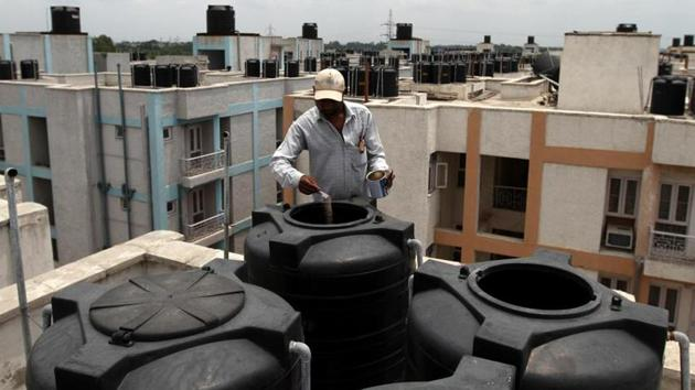 An MCD worker puts medicine in open water tanks.(HT File Photo)