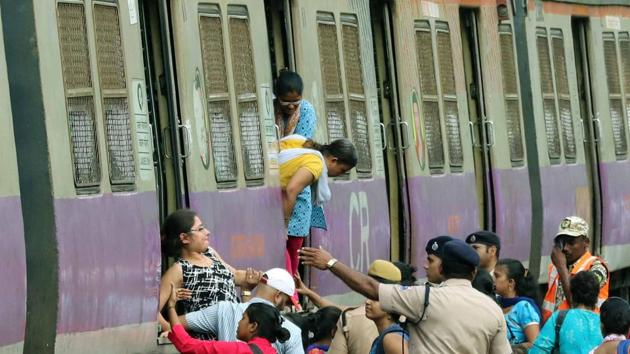 Commuters were forced to walk to Kalyan station after an overhead wire snapped on Wednesday.(HT Photo)