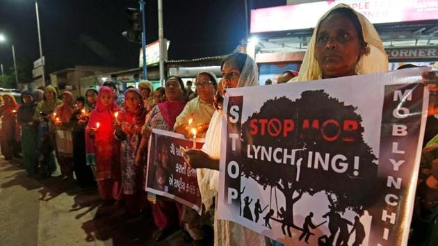 Women hold placards and candles during a protest against the recent mob lynchings across the country, in Ahmedabad.(REUTERS)