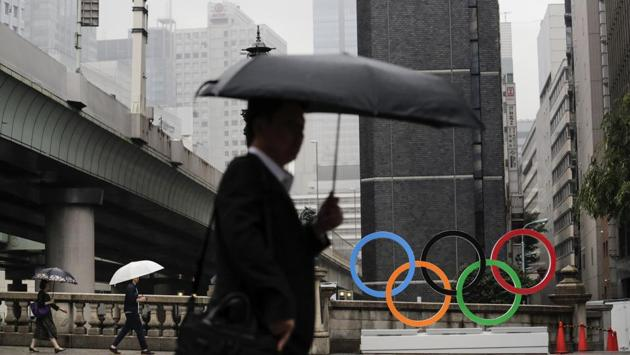 Commuters walk past the Olympic Rings in Tokyo. To mark the year-to-go stamp, the gold, silver and bronze Olympic medals were unveiled on July 23 as part of daylong ceremonies around the Japanese capital. Tokyo's 1964 Olympics showcased bullet trains, futuristic designs and a new expressway, underlining Japan's recovery following World War II. Those games were the first seen worldwide by early satellites, sending the Olympics into a new era. (Jae C. Hong / AP)