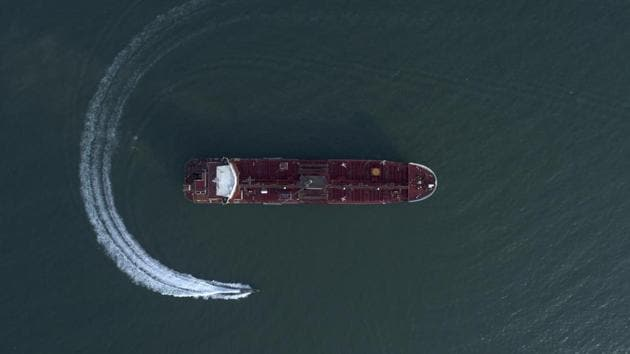 An aerial view shows a speedboat of Iran's Revolutionary Guard moving around the British-flagged oil tanker Stena Impero which was seized in the Strait of Hormuz on Friday by the Guard, in the Iranian port of Bandar Abbas. Global stock markets were subdued Monday while the price of oil climbed as tensions in the Persian Gulf escalated after Iran's seizure of a British oil tanker on Friday.(AP)