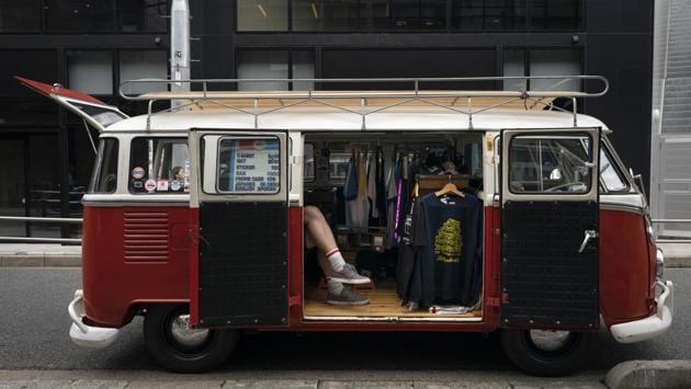 Bruce McCullough, who moved to Japan 22 years ago from Vancouver, Canada, sits in his mobile clothing store in the Shibuya district of Tokyo. (Jae C. Hong / AP)