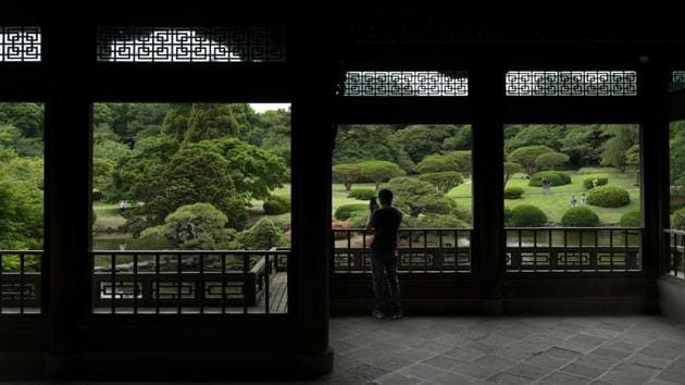 A tourist takes pictures from the Kyu Goryo-tei Pavilion in Shinjuku Gyoen national garden. Greater Tokyo has a population of more than 35 million — the world's largest metropolitan area. (Jae C. Hong / AP)