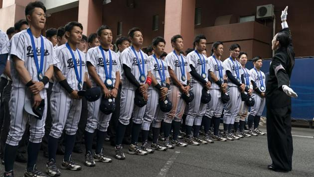 Bukkyo University cheerleading squad leader, Yamaguchi Karin (R) leads the school song in front of the school's baseball players. Roy Tomizawa, a Japanese American who lives in Japan and published the most definitive book on Tokyo's 1964 Olympics, said he applied for 16 tickets and got zero in the June lottery. (Jae C. Hong / AP)