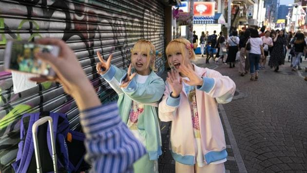 Twins, Kunika and Kuniho, 17, record a greeting for their social media followers in the Harajuku district of Tokyo. Harajuku is one of the most popular shopping neighbourhoods in Japan. (Jae C. Hong / AP)
