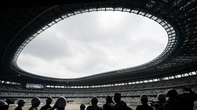 The media tours the new National Stadium in Tokyo. Despite scandals, rising costs and doubts about the economic payoff, the Tokyo Olympics will be a must-see event, if one can find a ticket or a hotel room. (Jae C. Hong / AP)
