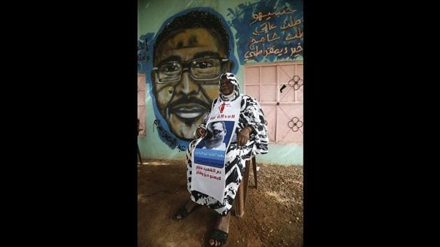 """Maiyssa Omar, the mother of Walid Abdelrahim sits in front of the mural painting of her son, ornating the family home. """"The painting keeps him alive,"""" she said, her voice choking as she talked of her son, who was killed during a three-day nationwide civil disobedience campaign in June. (Ashraf Shazly / AFP)"""