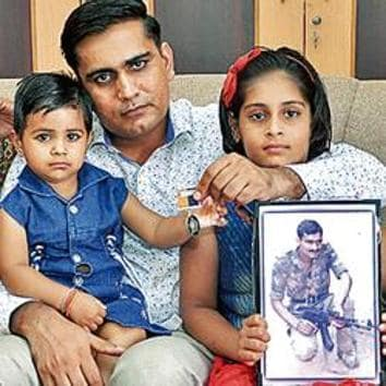 Kamla Devi (left), her older son, Devender Lamba, and granddaughters with a photo of her slain husband.(HT Photo)