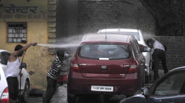 Man wash a car at a car-washing centre, in Noida, India.(Sunil Ghosh / Hindustan Times)