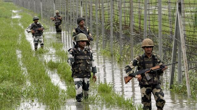 BSF personnel patrol the fence at International Border at Suchetgarh about 30 km from Jammu.(HT file)