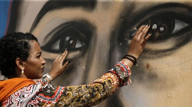 Sudanese activist Eythar Gubara, in front of a mural painting of Mohamed Mattar, on the wall of a youth club in Bahri. The colourful graffiti is part of a campaign to draw faces of protesters killed on June 3 and during the months-long protest movement against now ousted leader Omar al-Bashir on the walls of their family homes. (Ashraf Shazly / AFP)