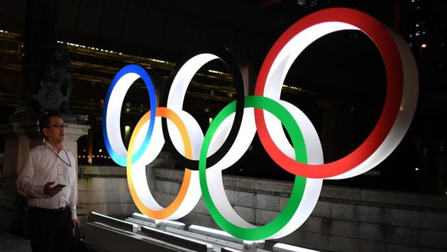 A man walks in front of the Olympic Rings displayed in the Tokyo's Nihonbashi district.(AFP)