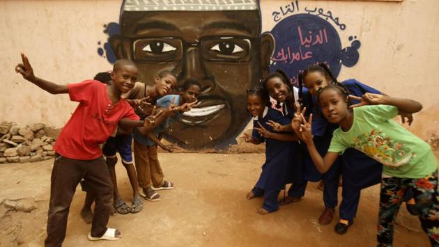 """Children gesture in front of a mural painting of a protester killed during the protest. Diab, who lives in the Qatari capital with her family but often returns to her homeland, said painting each mural costs her about $635. """"But martyrs took to the streets and died for us. This is the least we can do for them,"""" she said, who has drawn about 30 portraits of protesters killed in Khartoum. (Ashraf Shazly / AFP)"""