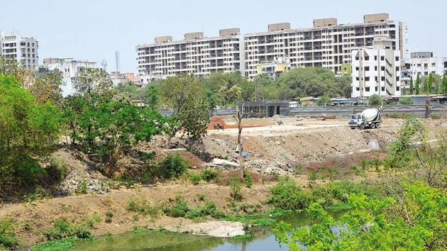 The Mutha river basin near Old Sangvi road has been encroached upon and construction work is in progress in the area currently.(HT PHOTO)