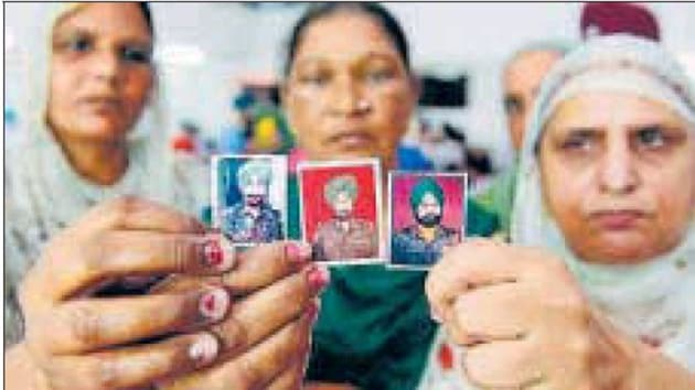 (From left) Wives of slain soldiers Kuldeep Singh, Prem Singh (C), Karnal Singh hold their husbands' photos before paying homage at a war memorial, on the outskirts of Amritsar on Friday.