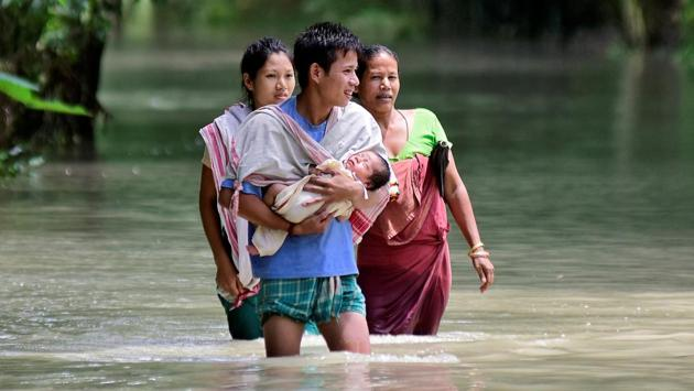 A man carries his new born baby as he and his family members wade through a flooded area to reach a relief camp at a village in Barpeta district Assam. (Anuwar Hazarika / REUTERS)