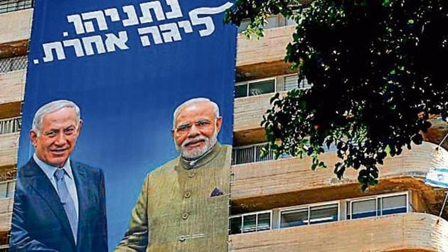 A Likud Party banner on a building in Tel Aviv shows Israeli PM Benjamin Netanyahu shaking hands with Indian PM Narendra Modi with a caption reading in Hebrew 'in a different league'. (AFP photo)