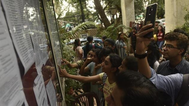 Students check the first merit list of FYJC, put up outside H R College at Churchgate in Mumbai on July 12.(HT FILE)