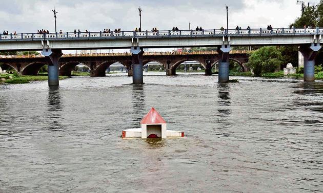 The water of Mutha river near Baba Bhide bridge was dangerously high on Sunday, after water was released from Khadakwasla dam.(Ravindra Joshi/HT PHOTO)