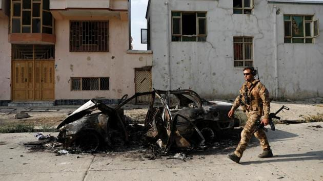 An Afghan security force walks past a burnt vehicle after Sunday's attack at the site in Kabul, Afghanistan July 29, 2019. REUTERS(REUTERS)
