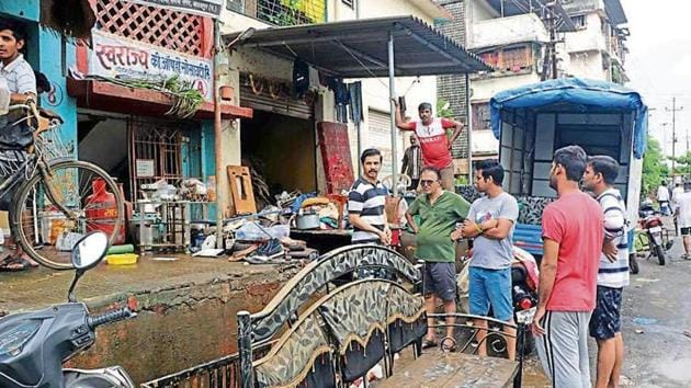 After Saturday's deluge, life is yet to return to normal for people in Badlapur. Here, residents of Rameshwadi stand outside their homes with whatever items they could salvage.(HT FILE)