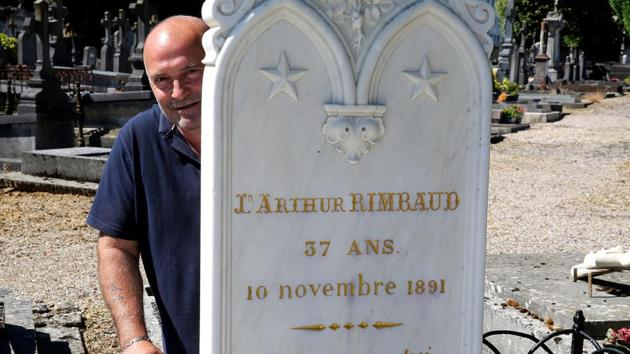 Bernard Colin, since 37 years guardian of the west cemetery of Charleville-Mezieres where French poet Arthur Rimbaud is buried, poses behind the grave stone at the poet's grave, in Charleville-Mezieres.(AFP)