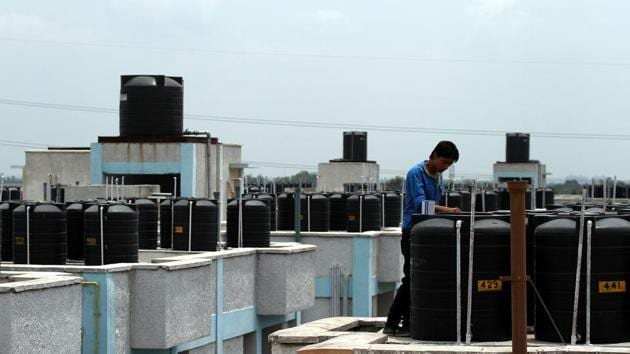 A file photo of water storage tanks on the top of buildings in Gurugram. Residents of sectors 81 to 98 might get supply of treated canal water by the end of September 2019.(Hindustan Times)