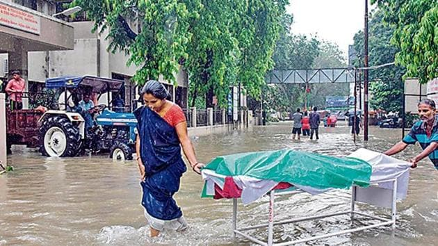 Workers push a gurney carrying a dead body as they wade through the waterlogged campus of a Vadodara hospital.(AFP)