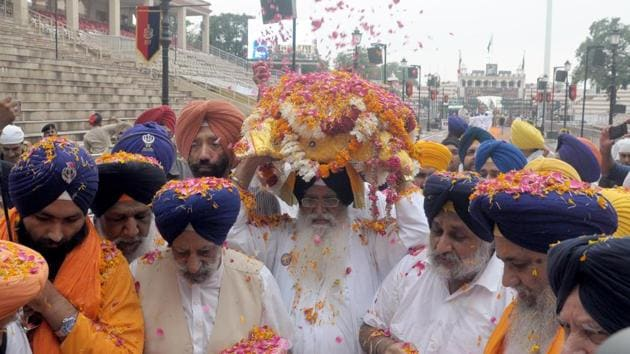 Head priest of Golden Temple, Giani Jagtar Singh (C) carries the Guru Granth Sahib during the 'Nagar Kirtan' procession to mark the 550th birth anniversary of Guru Nanak Dev, at the Wagah Border Post, on Thursday, August 1, 2019.(Sameer Sehgal / HT Photo)