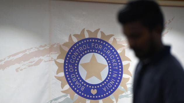A man walks in front of the logo for the Board of Control for Cricket in India (BCCI)(AFP)