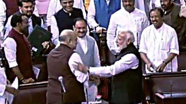 Prime Minister Narendra Modi greets Union Home Minister Amit Shah after the Jammu and Kashmir Reorganisation Bill being passed by Rajya Sabha.(ANI)
