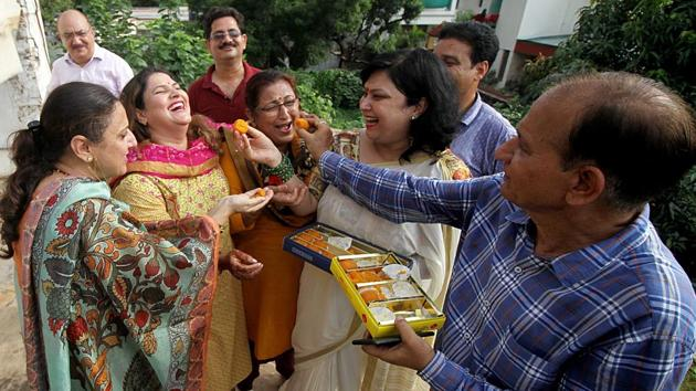 Kashmiri Pandits offer sweets to each other as they celebrate after scrapping of article 370 from Jammu and Kashmir.(ANI Photo)