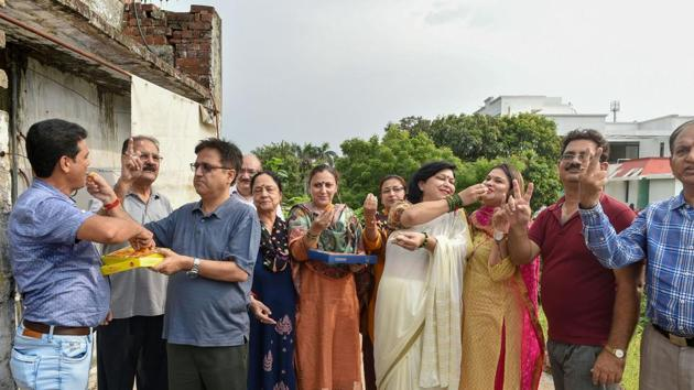 Lucknow: Kashmiri Pandits distribute sweets as they celebrate the Union government's move to revoke Article 370 in Jammu and Kashmir, in Lucknow, Monday, Aug 5, 2019.(PTI)