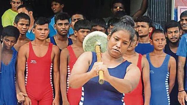 A woman wrestler swinging a mace at an event to mark Nag Panchami in Varanasi, Monday, August 5, 2019.(HT Photo)