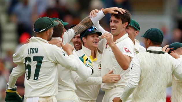 Australia's Pat Cummins and Steve Smith celebrate with teammates after taking the wicket of England's Chris Woakes giving Australia victory in the first test(Action Images via Reuters)
