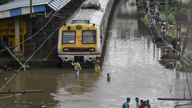 People walk on water logging track at Chunabhati railway station in Mumbai. Central Railway (CR) cancelled 23 outstation trains on Monday, including Deccan Queen and Pragati Express.(Kunal Patil/HT Photo)