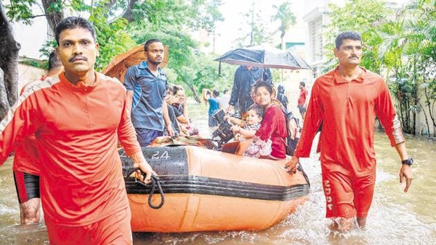 NDRF team rescues residents of Prathamesh Park, Baner in Pune on Monday using lifeboat.(MILIND SAURKAR/HT)