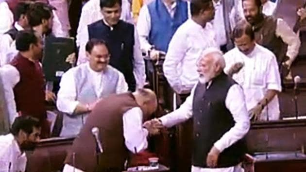 Prime Minister Narendra Modi greets Union Home Minister Amit Shah after the Jammu and Kashmir Reorganisation Bill being passed by Rajya Sabha in New Delhi on Monday. (ANI Photo)