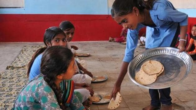 School kids eating chapati and daal with salt which were served to them during interval as mid-day meal(Hindustan Times via Getty Images)
