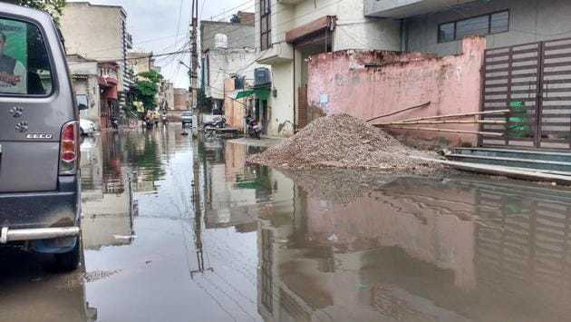 Feroz Gandhi colony, which is near the section of Basai Road that caved because of a pipeline leakage, has been flooded with sewage water since the repair work started on Saturday.(HT Photo)
