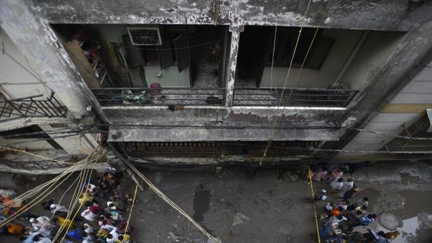 People gathered around the location of a fire that broke out in a multi-storey building in Okhla's Zakir Nagar in the early hours of the day.(Burhaan Kinu/HT PHOTO)