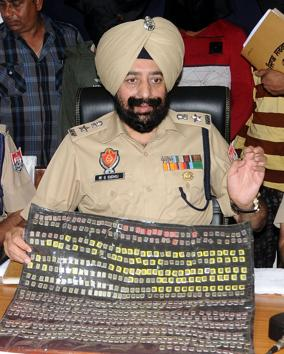 Patiala SSP Mandeep Singh Sidhu showing the 693 SIM cards recovered from the accused, who made 23 transactions over three days in Patiala MP Preneet Kaur's account.(Bharat Bhushan / HT Photo)
