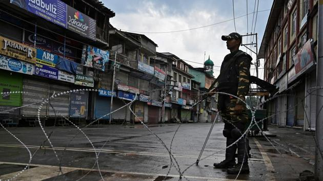 Security personnel stands guard on a street during a curfew in Srinagar on Thursday.(AFP File)