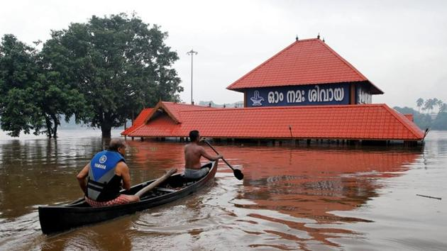 Members of a rescue team row a boat towards a submerged temple to look for stranded people on the outskirts of Kochi in Kerala.(Reuters Photo)